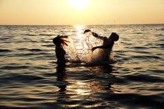 Fille et garçon ayant l'amusement, nageant en mer Image libre de droits