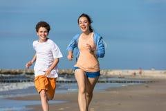 Fille et garçon courant sur la plage Photo stock