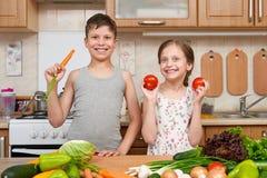 Fille et garçon d'enfant ayant l'amusement avec les tomates et la carotte Intérieur à la maison de cuisine avec des fruits et lég Photographie stock