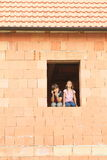 Fille et garçon dans la fenêtre Photo libre de droits