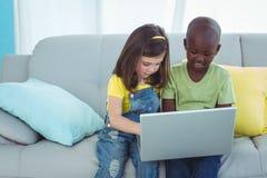 Fille et garçon de sourire à l'aide d'un ordinateur portable Photo stock