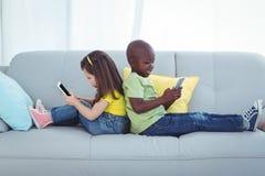 Fille et garçon de sourire à l'aide des téléphones portables Images stock