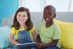 Fille et garçon de sourire à l'aide du comprimé Image stock
