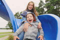 Fille et garçon de sourire ayant l'amusement sur la glissière du ` s d'enfants Images libres de droits