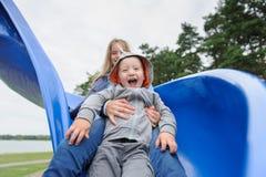 Fille et garçon de sourire ayant l'amusement sur la glissière du ` s d'enfants Photographie stock libre de droits