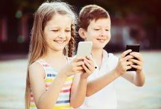 Fille et garçon de sourire regardant des téléphones portables en parc Image stock