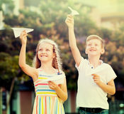 Fille et garçon jouant les avions de papier Photo libre de droits