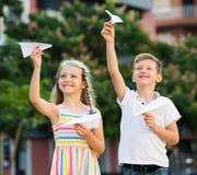 Fille et garçon jouant les avions de papier Photographie stock libre de droits