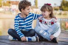 Fille et garçon jouant sur la plage Photo stock