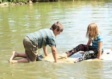 Fille et garçon jouant sur le ressac Images libres de droits