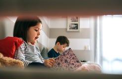 Fille et garçon lisant un livre Photo stock