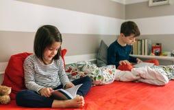 Fille et garçon lisant un livre Photographie stock libre de droits
