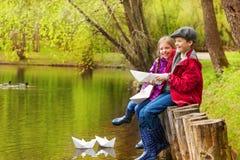Fille et garçon riants près d'étang avec les bateaux de papier Photos libres de droits