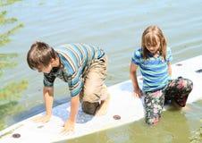 Fille et garçon jouant sur le ressac Photographie stock