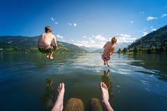 Fille et garçon sautant dans l'eau de lac Photographie stock libre de droits