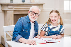 Fille et homme supérieur dans des lunettes se reposant à la table avec le livre et souriant à l'appareil-photo Photo libre de droits