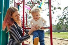 Fille et mère d'enfant jouant l'échelle de terrain de jeu photos libres de droits