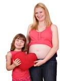 Fille et mère enceinte avec le coeur rouge Images stock