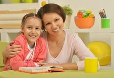 Fille et mère lisant le livre Images stock