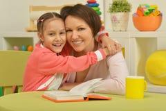 Fille et mère lisant le livre Photographie stock