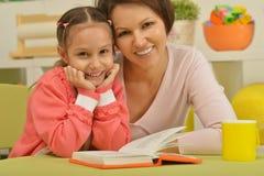 Fille et mère lisant le livre Image stock