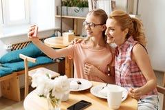 Fille et mère prenant un selfie dans un café Photographie stock