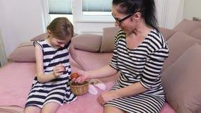 Fille et mère s'asseyant sur le lit et essayer le combat d'oeuf de pâques banque de vidéos