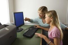 Fille et maman sur l'ordinateur. images stock