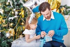 Fille et père avec des cadeaux à l'arbre de Noël Photos stock