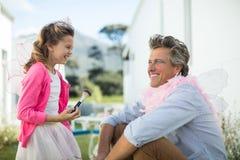 Fille et père dans le costume féerique ayant l'amusement au jardin Photo stock