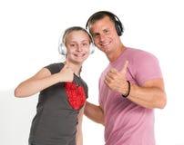Fille et père de sourire dans des écouteurs écoutant la musique Photo libre de droits