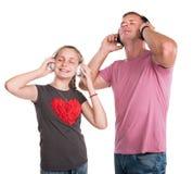 Fille et père de sourire dans des écouteurs Image libre de droits