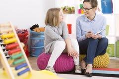 Fille et psychologue s'asseyant sur des poufs Photos libres de droits
