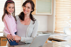 Fille et sa mère à l'aide d'un carnet Images stock