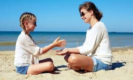 Fille et sa maman jouant avec le sable sur la plage Photographie stock libre de droits