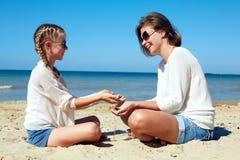 Fille et sa maman jouant avec le sable sur la plage Image stock