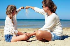 Fille et sa maman jouant avec le sable sur la plage Image libre de droits