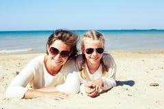 Fille et sa maman jouant avec le sable sur la plage Images stock