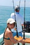 Fille et sa pêche de père sur un bateau Photos libres de droits
