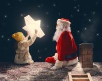 Fille et Santa Claus s'asseyant sur le toit Photo stock