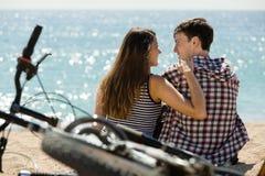 Fille et son ami sur la plage près des vélos Image stock