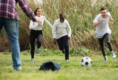 Fille et trois garçons jouant le parc et le sourire du football au printemps Photographie stock
