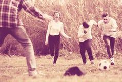 Fille et trois garçons jouant le parc et le sourire du football au printemps Photo stock