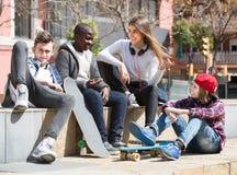Fille et trois garçons traînant dehors et discutant le somethin Photo libre de droits