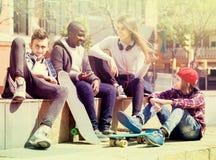 Fille et trois garçons traînant dehors et discutant le somethin Photographie stock libre de droits