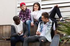 Fille et trois garçons traînant dehors et discutant le somethin Images stock