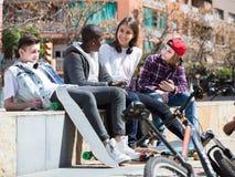 Fille et trois garçons traînant dehors et discutant le somethin Image libre de droits
