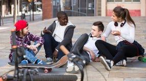 Fille et trois garçons traînant dehors et discutant le somethin Photographie stock