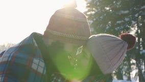 Fille et type affectueux dans la forêt d'hiver de jour ensoleillé de bras, fusée de lumière du soleil banque de vidéos
