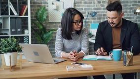 Fille et type discutant la stratégie d'idées d'affaires écrivant dans le carnet dans le bureau banque de vidéos
